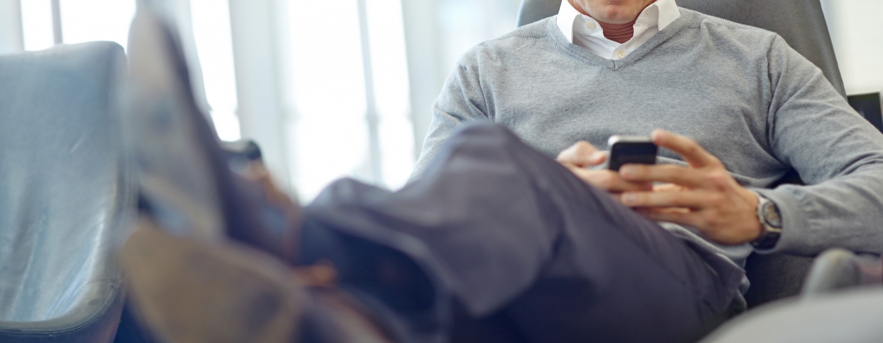 lifestyle image of a person relaxed in a chair while looking at their mobile device